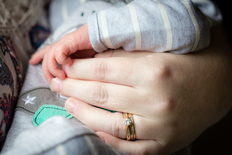 newborn rests tiny hand on top of mothers hand