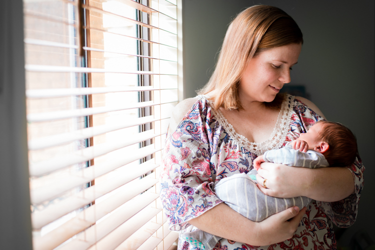 mother cradles newborn baby by window during in-home photo sessi