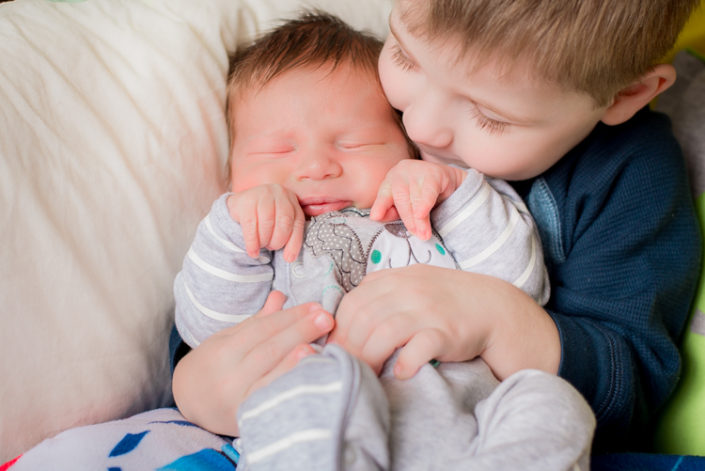 big brother cuddles newborn baby at in-home photo session