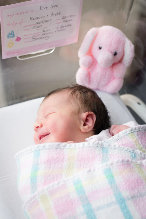 newborn smiles in hospital bassinet