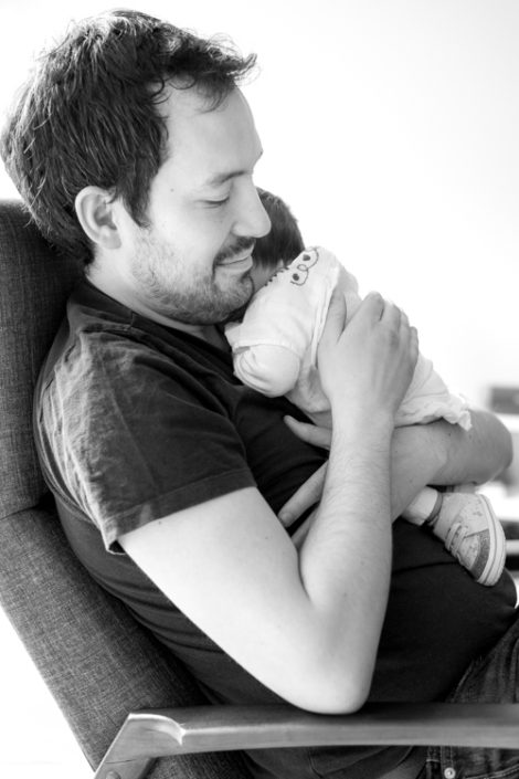 newborn cuddled against dads chest