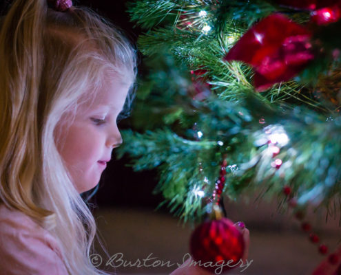 little girl holds christmas tree bauble by christmas tree