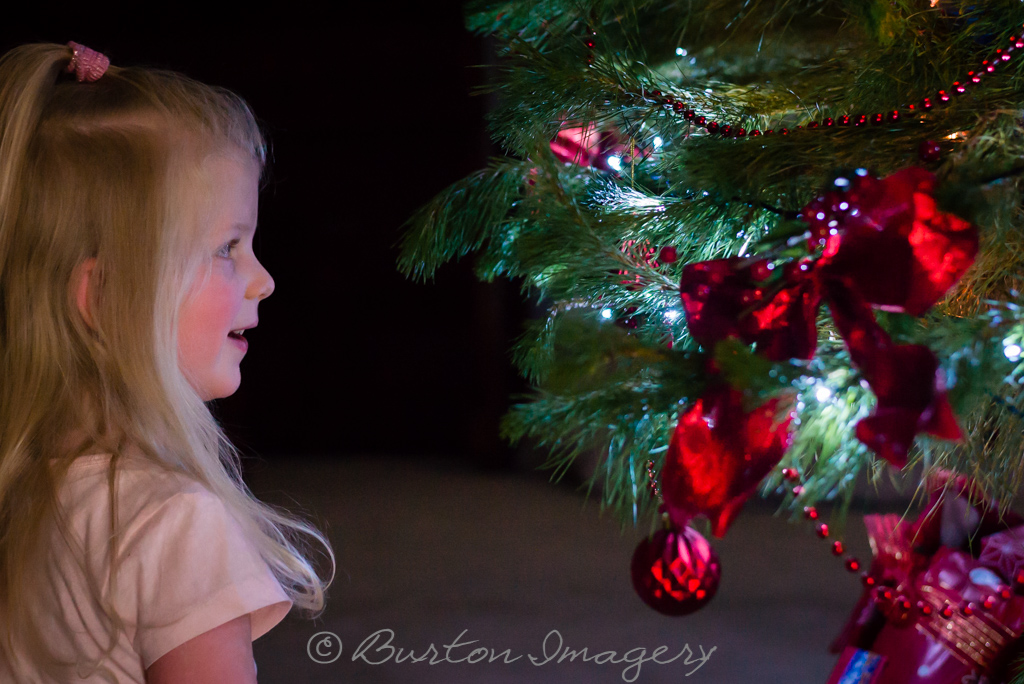 little girl smiles as she looks at the decorated christmas tree in her home