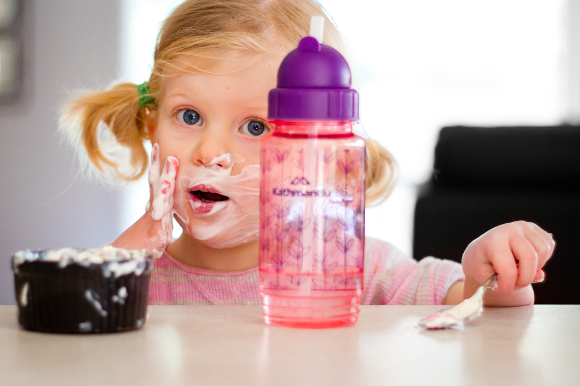 little girl smears yogurt on face sitting at kitchen table in a natural photo