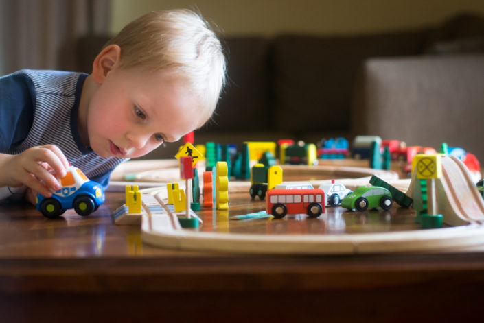 little boy plays with train set at home