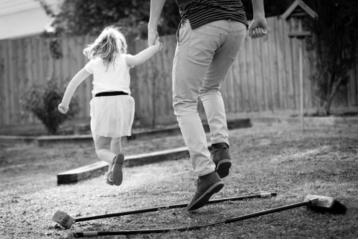 dad and daughter hold hands and jump over obstacle course