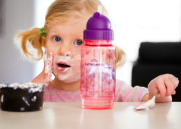 little girl smears yogurt on face sitting at kitchen table