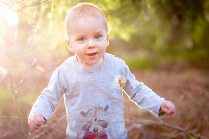 toddler boy stands outside with sunlight glowing behind him