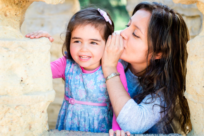 mum whispers a secret to her little girl who laughs at Tim Neville Arboretum