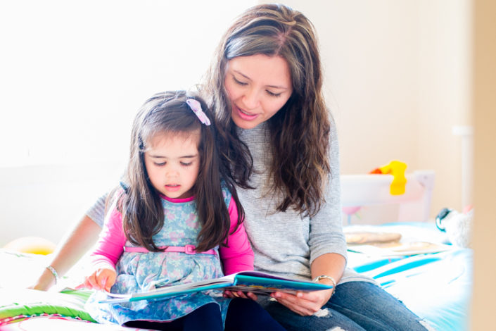 mum and daughter sit on the bed reading a storybook