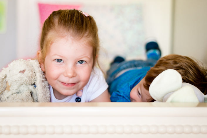 siblings play on bed together during lifestyle photo session