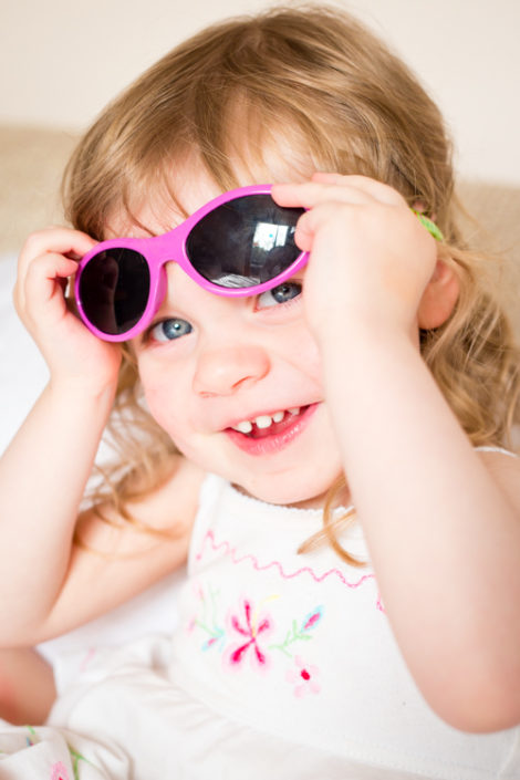little girl lifts toy sunglasses up her head and smiles at home photo session in eastern suburbs