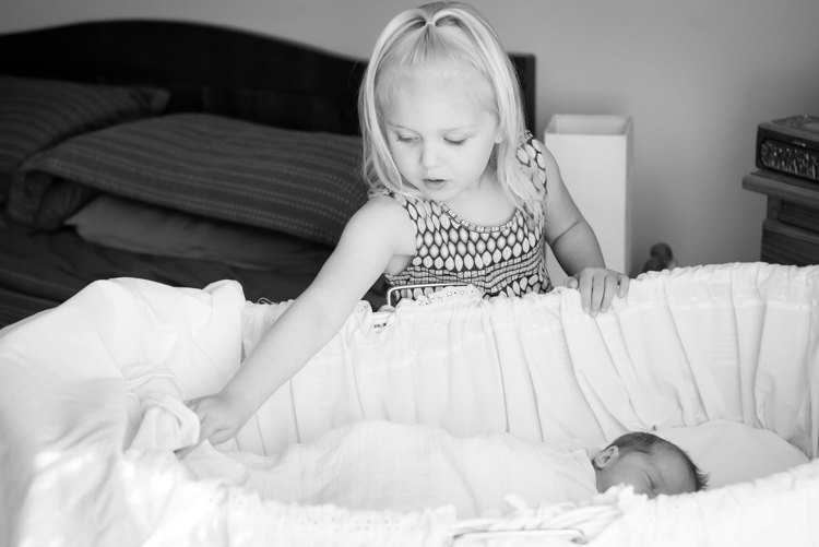 big sister helps with blankets in bassinet for newborn sister