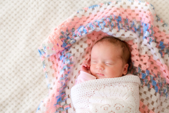 newborn baby girl lays sleeping on a knitted blanket during in-ho