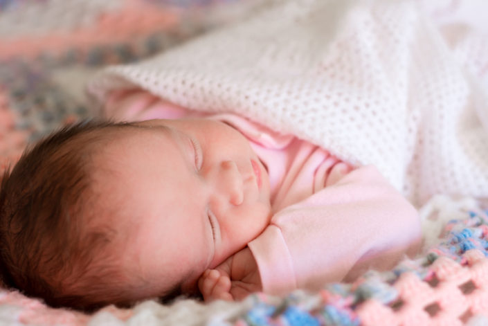 newbon baby girl lays sleeping on a knitted blanket during in-home photo session