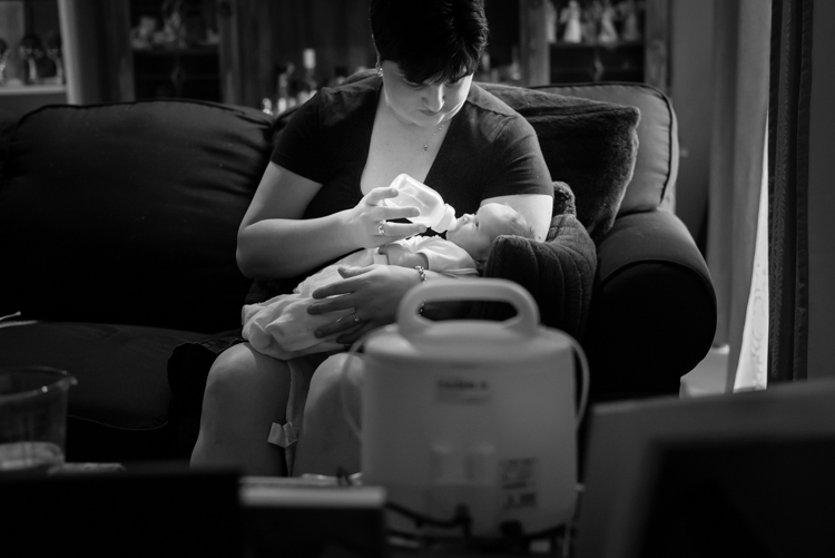 mother feeds breast milk to young newborn on couch