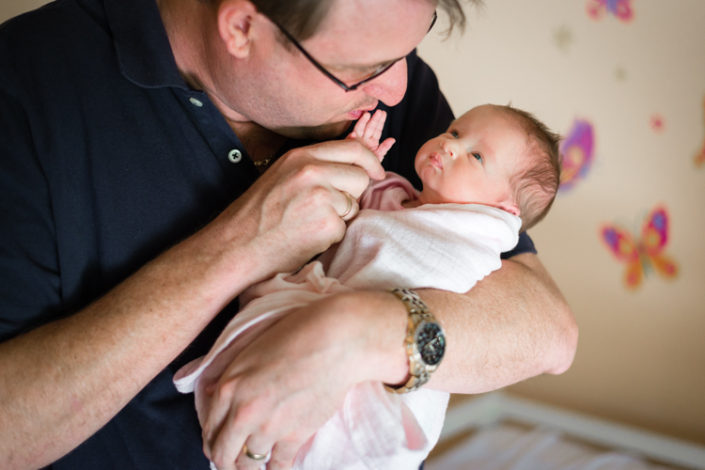 father cradles and kisses newborn baby girls little fingers in n