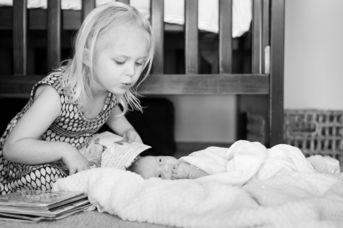big sister reads storybooks to newborn baby girl laying on a bla