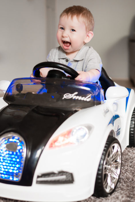 baby laughs as he sits in ride-on car