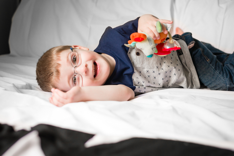 toddler lays on bed holding his favourite teddy