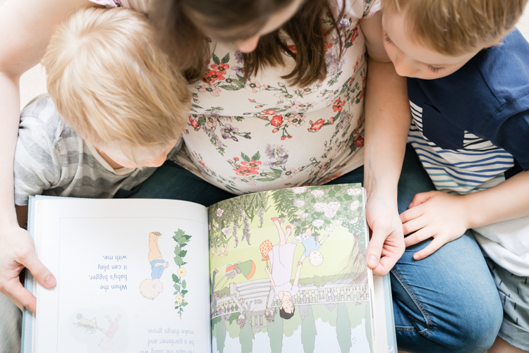 pregnant mother reading with siblings