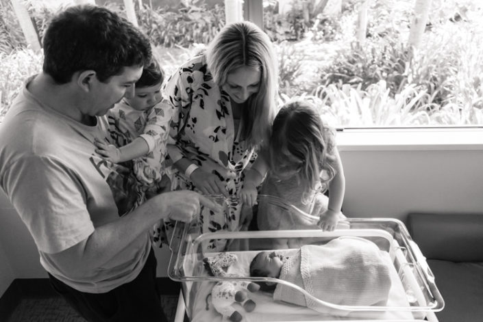 family looking at newborn in hospital bassiset