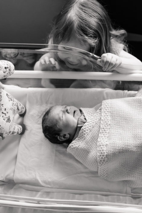 sister looks through hospital bassinet at newborn