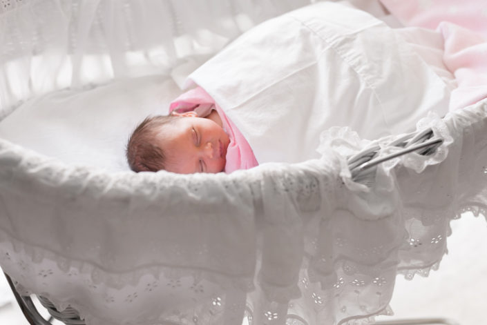 newborn sleeping in white bassinet